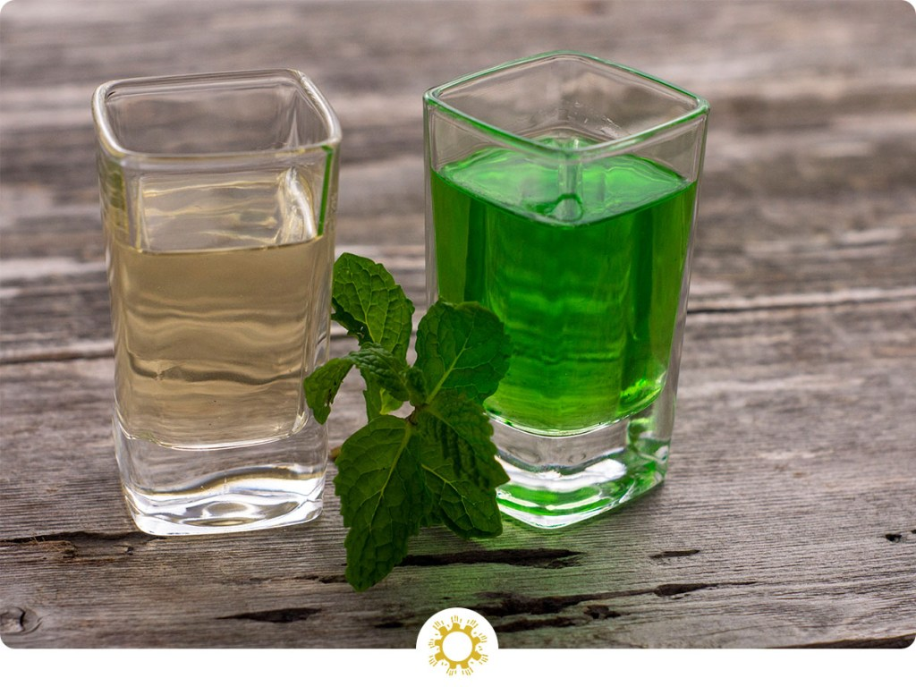 Two square glass shot glasses with clear creme de menthe in one and green creme de menthe in the other with a sprig of mint between on a wooden surface (with logo overlay)