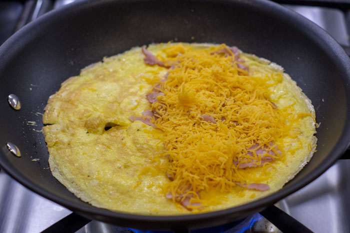 Cooked eggs in a skillet with ham and cheese on half of the eggs