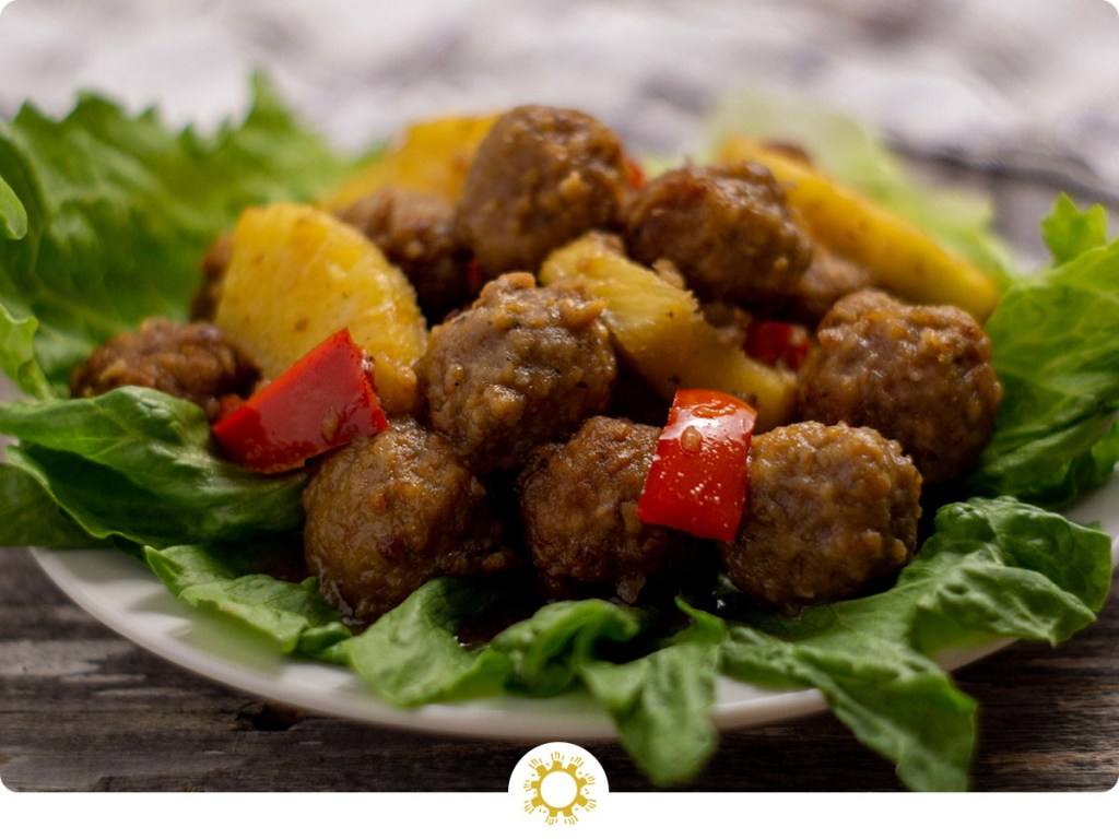 Hawaiian meatballs with pineapple chunks and chopped red peppers on a bed of lettuce on a round white plate with a white and brown towel behind all on a wooden surface (with logo overlay)