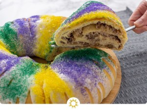 Round King Cake decorated with white glaze and yellow, green, and purple sprinkles with a slice being lifted out to show the rolled cake with cream cheese and pecan filling (with logo overlay)