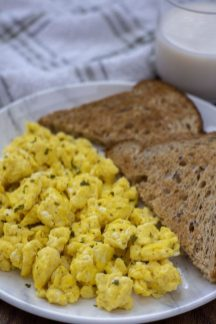 Fluffy and Yummy Scrambled Eggs on a round white plate with two slices of triangle-cut toast next to a glass of milk and a white and grey towel all on a wooden surface (vertical)