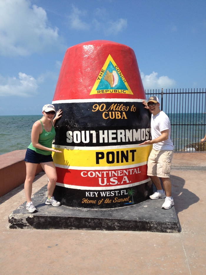 Man and woman next to the Southermost Point buoy in Key West, Florida
