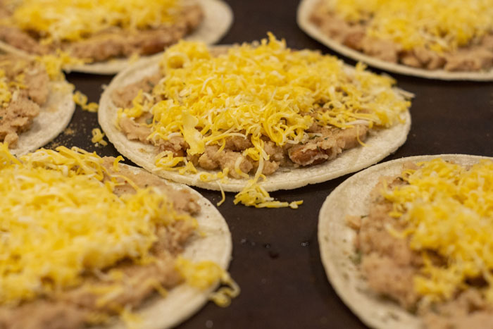 Corn tortillas on a baking stone topped with refried beans and shredded cheese