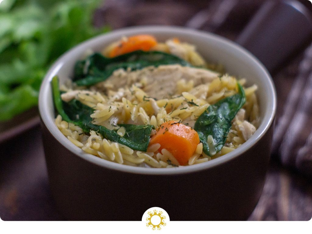 Chicken Orzo Pasta in a brown bowl next to a plate with spinach leaves and a brown towel on a wooden surface (with logo overlay)