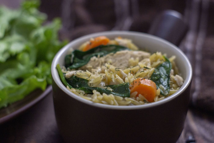 Chicken Orzo Pasta in a brown bowl next to a plate with spinach leaves and a brown towel on a wooden surface