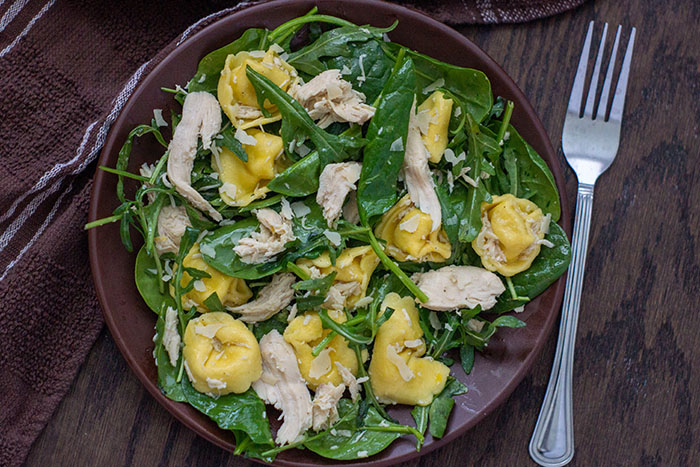 Chicken Tortellini Salad with Lemon Dressing on a round brown plate next to a fork on a wooden surface