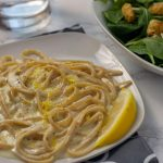 Creamy Lemon Pasta on a square white plate with a salad and glass of water in the background (with title overlay)
