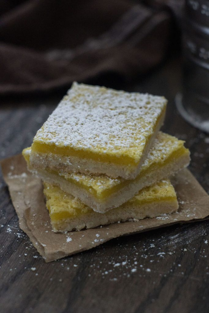 Three lemon bars stacked on top of each other sprinkled with powdered sugar sitting on a piece of brown paper on a wooden surface (vertical)