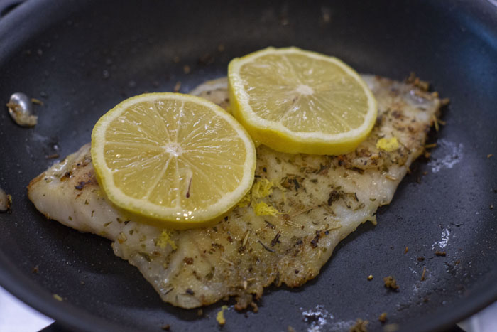 Close up of tilapia in a skillet with lemon slices on top