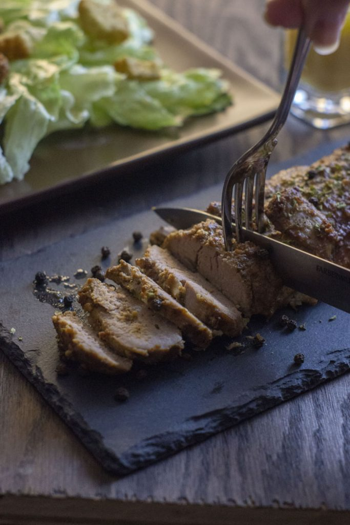 Marinated Baked Pork on a dark granite platter on a wooden surface with a fork and knife cutting it into slices and a salad on a brown plate in the background