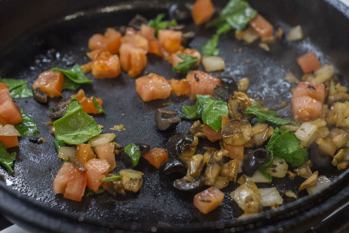 Vegetables being sauteed in a cast iron skillet