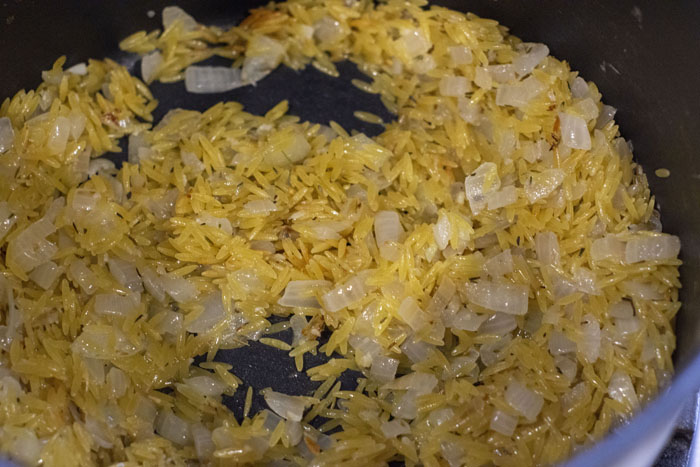 Close up of orzo and lemon toasting in a large stock pot