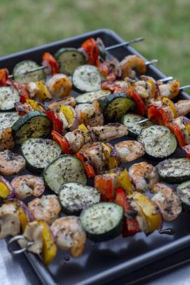 Summer Basil Chicken and Shrimp Kabobs on a metal sheet pan with grass in the background (vertical)