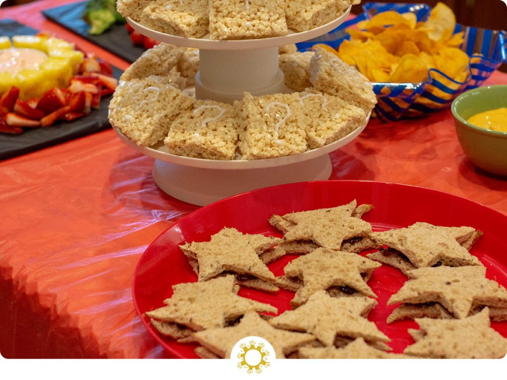 Super Easy Super Mario Themed Food with question block rice krispies and star shaped sandwiches on a red tablecloth (with logo overlay)
