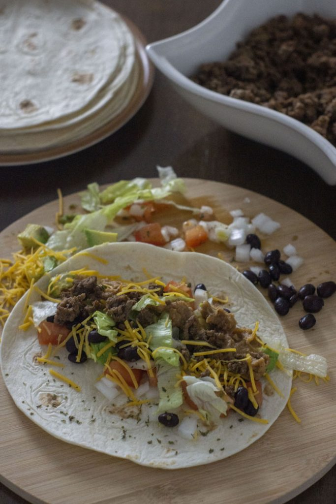 Taco with all of the toppings on a wooden board with other toppings around it and a plate of shells in the background next to a bowl of taco meat