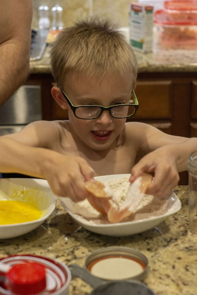 Young boy in glasses dipping chicken into a bowl of flour