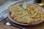 Tortilla-Crusted Chicken next to seasoned rice on a brown plate with a towel and fork next to the plate