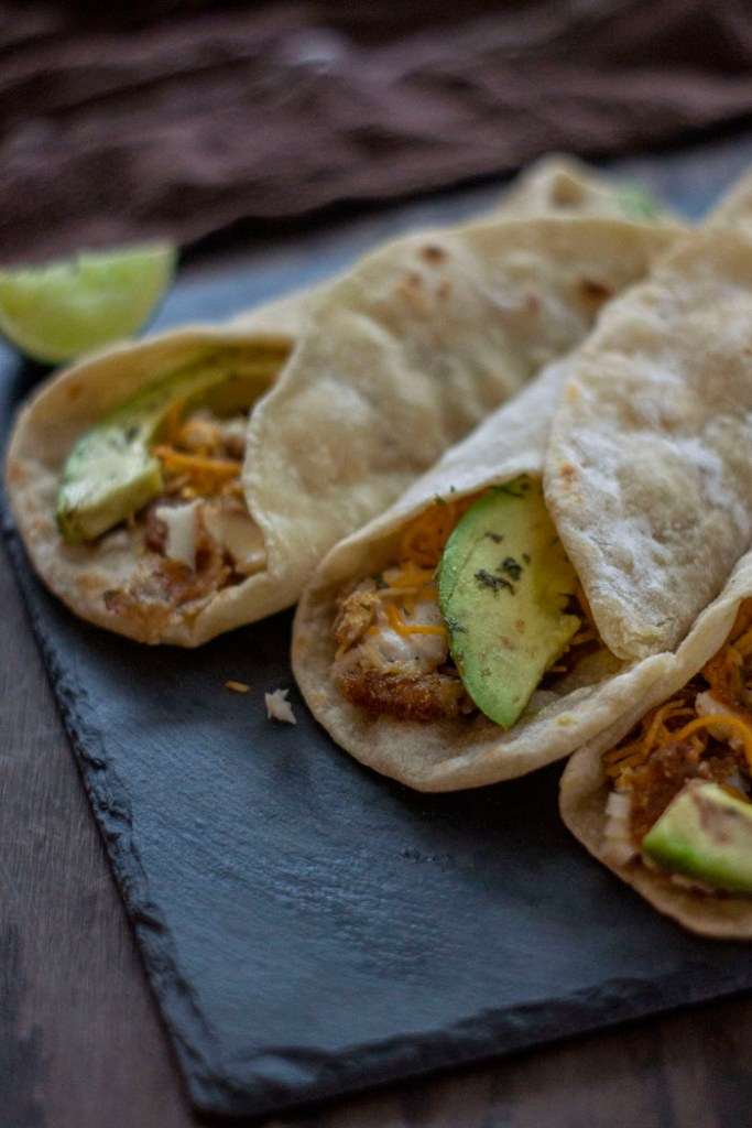 Avocado fish tacos rolled up and ready to eat (vertical)