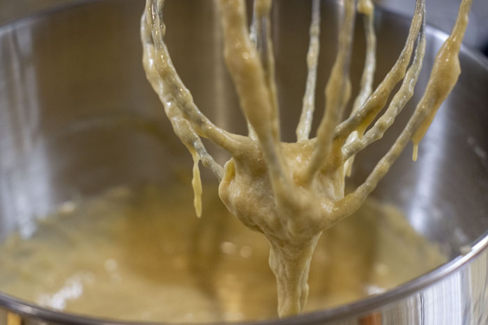 Whisk attachment with banana bread batter dripping off of it