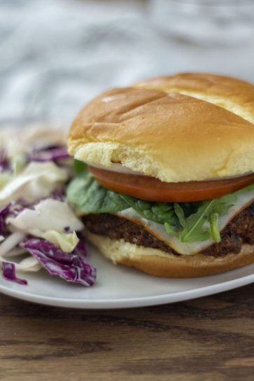BBQ burger on a white plate next to coleslaw on a wooden background (vertical)
