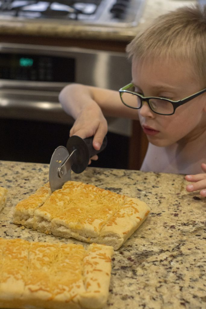 Young boy using a pizza cutter to divide cooked breadsticks