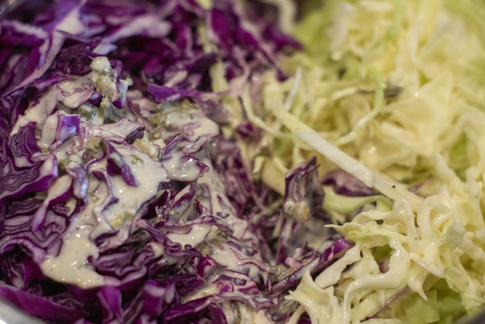 Close up of purple and green cabbage with coleslaw dressing