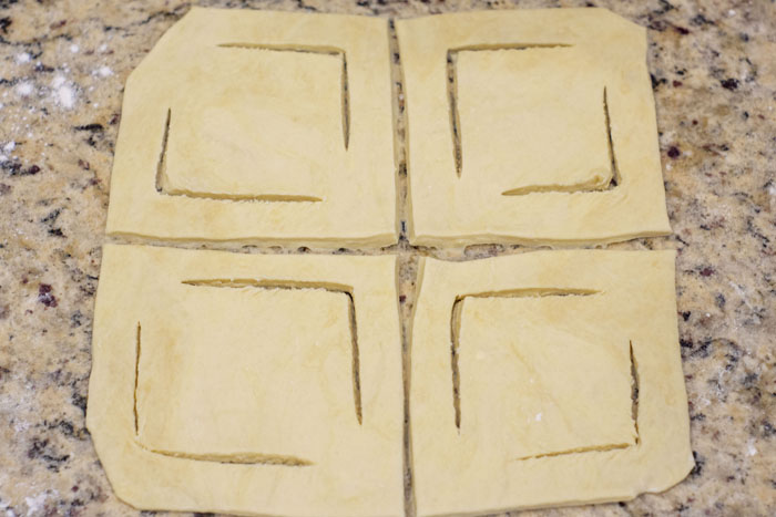 Puff pastry rolled out and cut into quarters with corners cut for folding