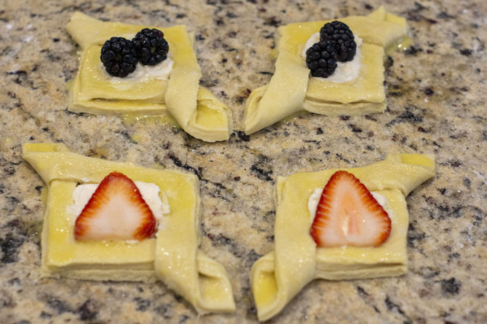 Puff pastry folded into diamonds filled with cream cheese and fruit
