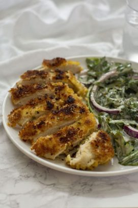 Sliced crispy chicken with salad next to it on a round white plate (vertical)