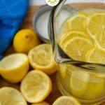 Lemonade in a glass pitcher next to juiced lemons on a wooden board with a blue towel to the side (with title overlay)