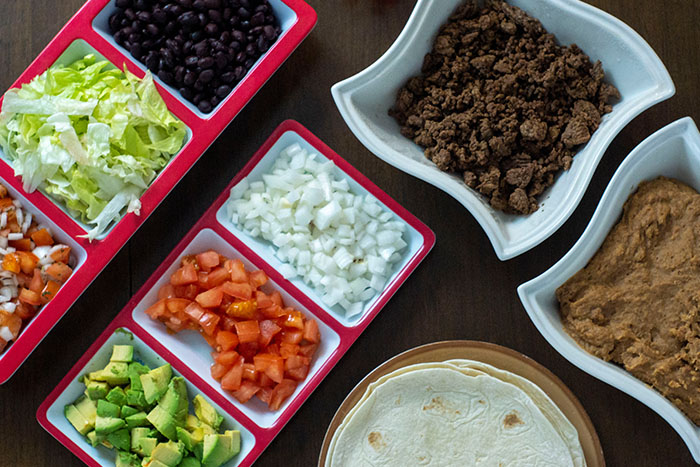 Taco bar on a wooden surface with multiple dishes of ingredients