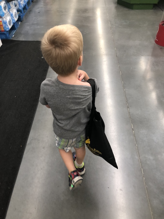 Young boy walking in grocery store with a reusable bag over his shoulder