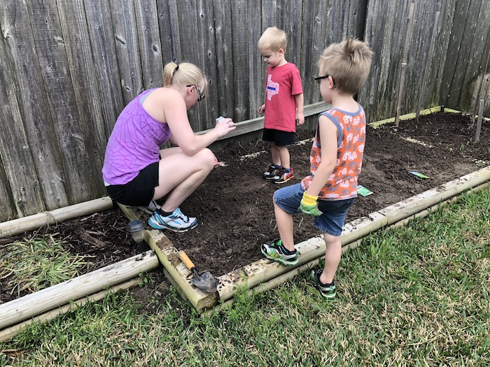 Two young boys helping mom plant an outdoor garden