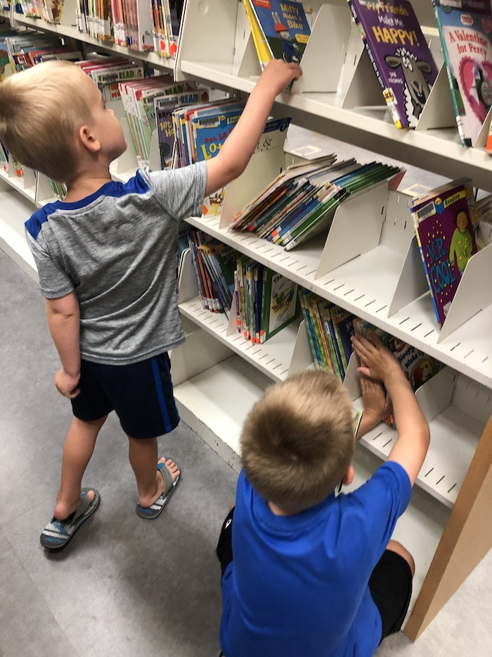 Two young boys picking books at the library