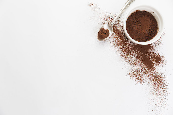 Cocoa powder in a white dish with some spilled out next to a spoon