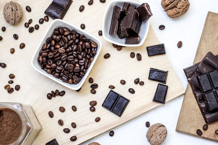 Overhead shot of coffee beans in a bowl, chocolate in another bowl, and pieces of chocolate and coffee beans on a wooden surface