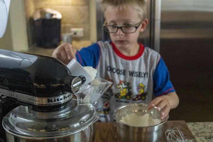 Young boy pouring flour into a stand mixer