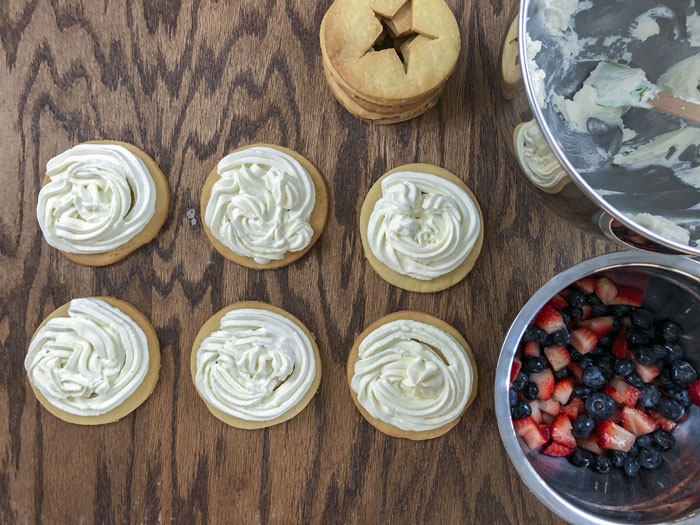 Cornmeal cookies with cream cheese filling and bowl of fruit