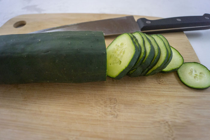 Cucumber on a cutting board with half of it sliced and a chef knife behind it