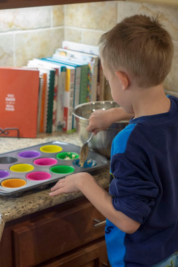 Young boy adding muffin mix to silicone muffin cups