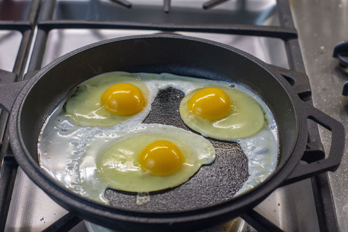 Three raw eggs in a cast-iron skillet