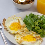 Two over-hard fried eggs next to spinach and arugula on a round white plate with a white bowl of breakfast potatoes and a glass of orange juice behind all on a wooden surface (with title overlay)