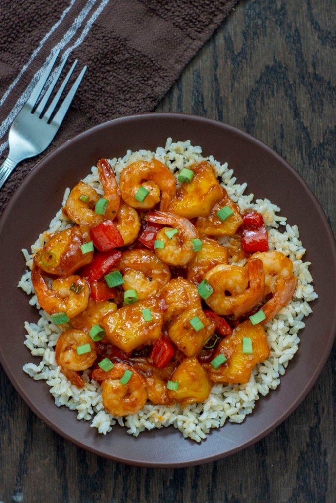 Pineapple shrimp stir-fry over a bed of rice garnished with green onion on a brown plate on a wooden surface with a towel and fork to the left side (vertical)