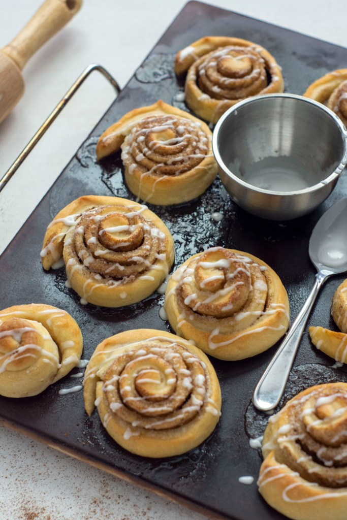 Baked cinnamon rolls on a baking stone with a small bowl of icing and a spoon on the pan on a white surface next to a wooden rolling pin (vertical)