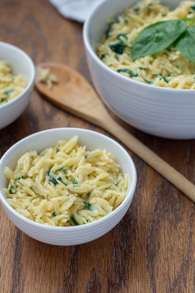 Cheesy Spinach Orzo Pasta Sides in a small white bowl next to a wooden spoon with two more bowls in the background all on a wooden surface (vertical)
