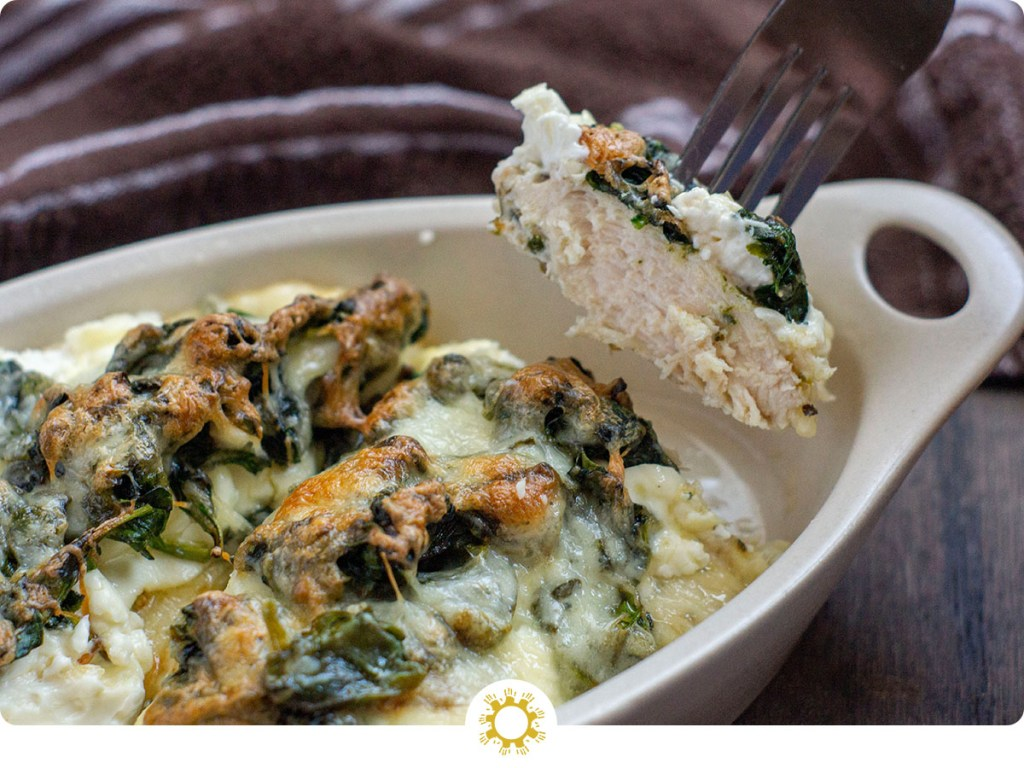 Chicken and Spinach Casserole with Cream Cheese in a tan bowl on a wooden surface with a piece of chicken held up on a fork (with logo overlay)