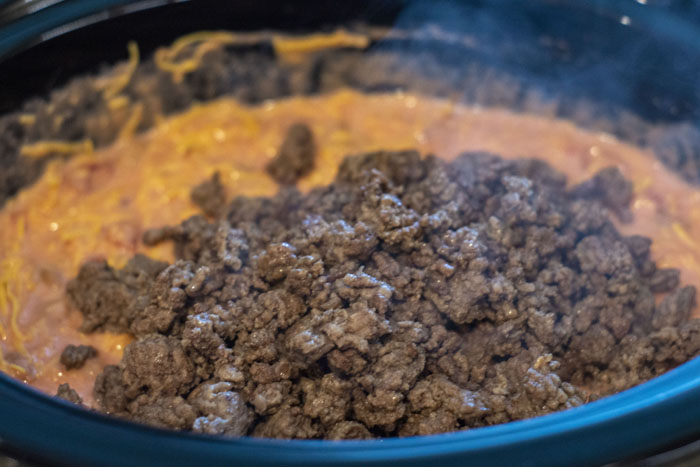 Chili nacho dip in the slow cooker with ground beef on top ready to be mixed in