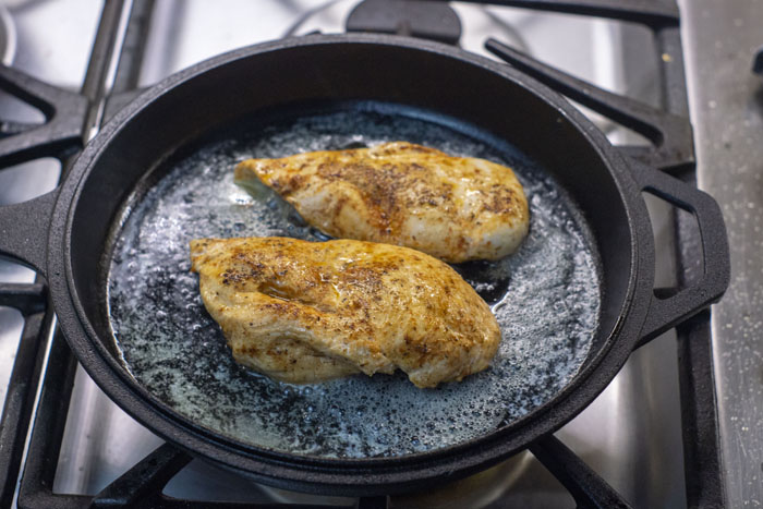 Two seasoned chicken breasts in a cast iron skillet over a gas stovetop