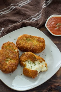 Fried mozzarella cakes with one broken open to show the cheese on a white plate next to a white bowl of marinara sauce with a brown towel in the background all on a dark wooden surface (vertical)