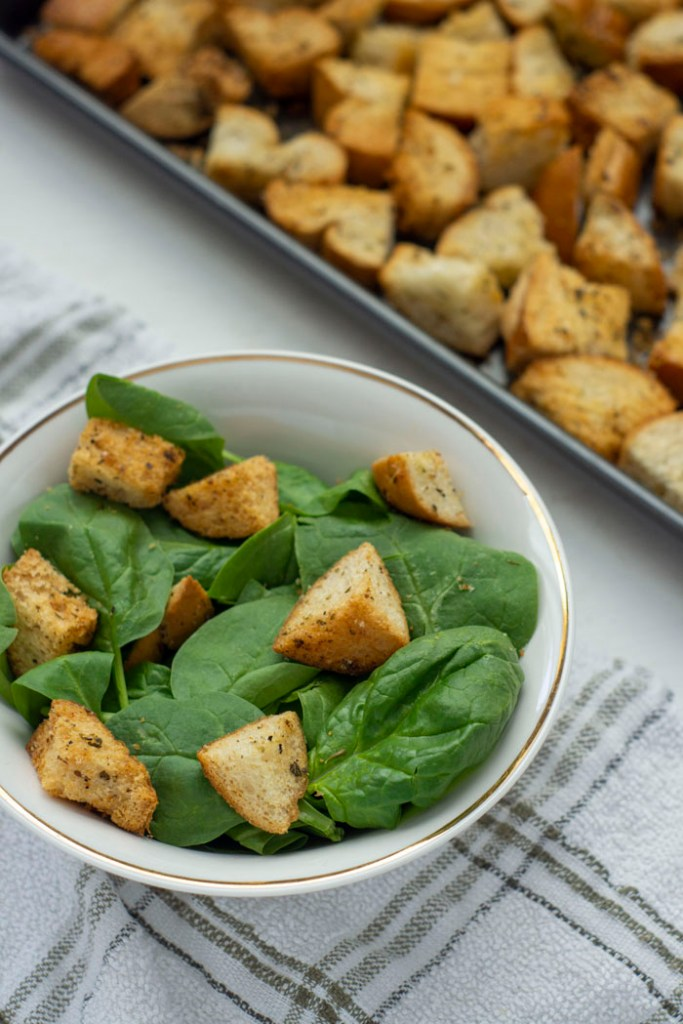 Italian-Style croutons on top of spinach leaves in a white bowl on top of a white and brown towel next to a metal baking sheet (vertical)